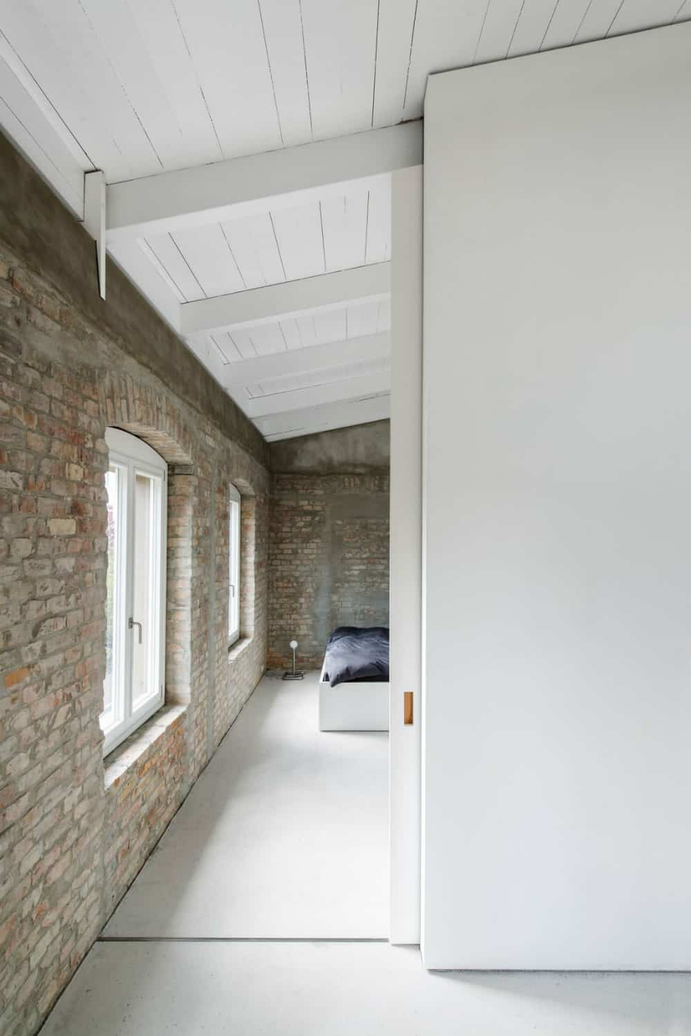 Bedroom has the same exposed brick walls