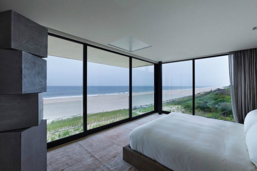 Bedroom's glass walls overlook the beach