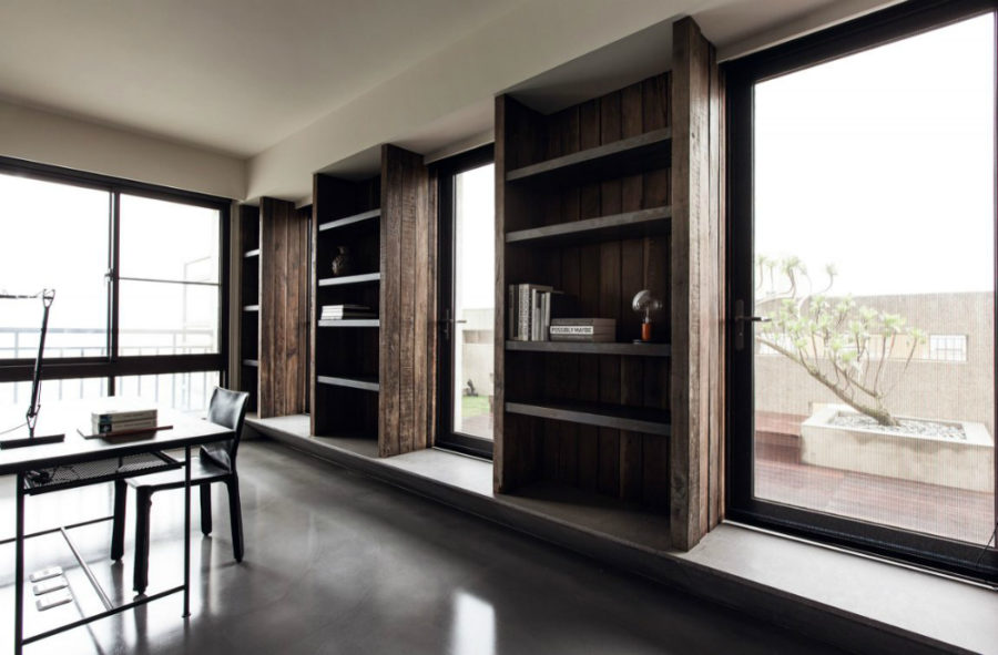 Built-in open shelving units in the home office interchange with huge windows