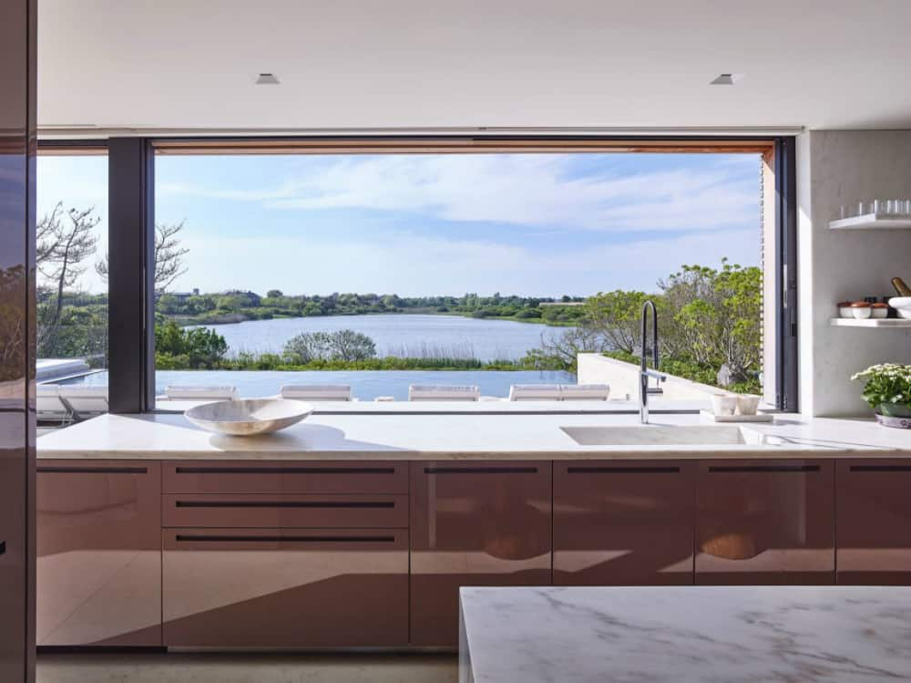 Contemporary glossy kitchen cabinets have an unusual mauve color