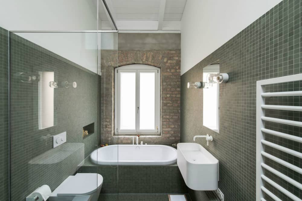 Even the green-tiled bath has a featured brick wall