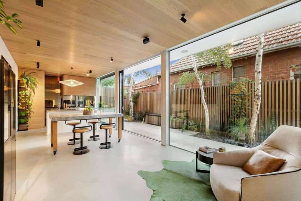 Kitchen and dining area visually shares space with the backyard thanks to sliding glass walls