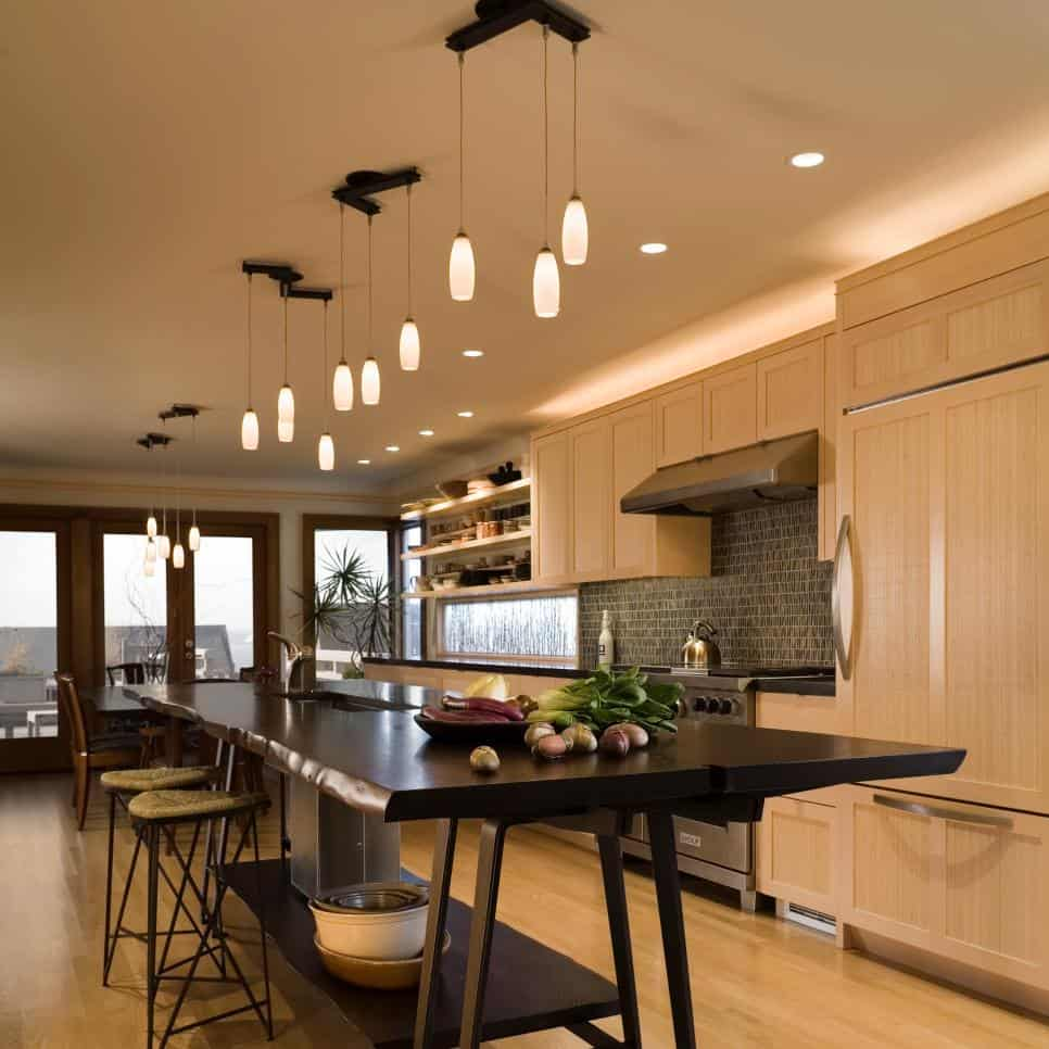 Kitchen with a table kitchen island by FINNE Architects