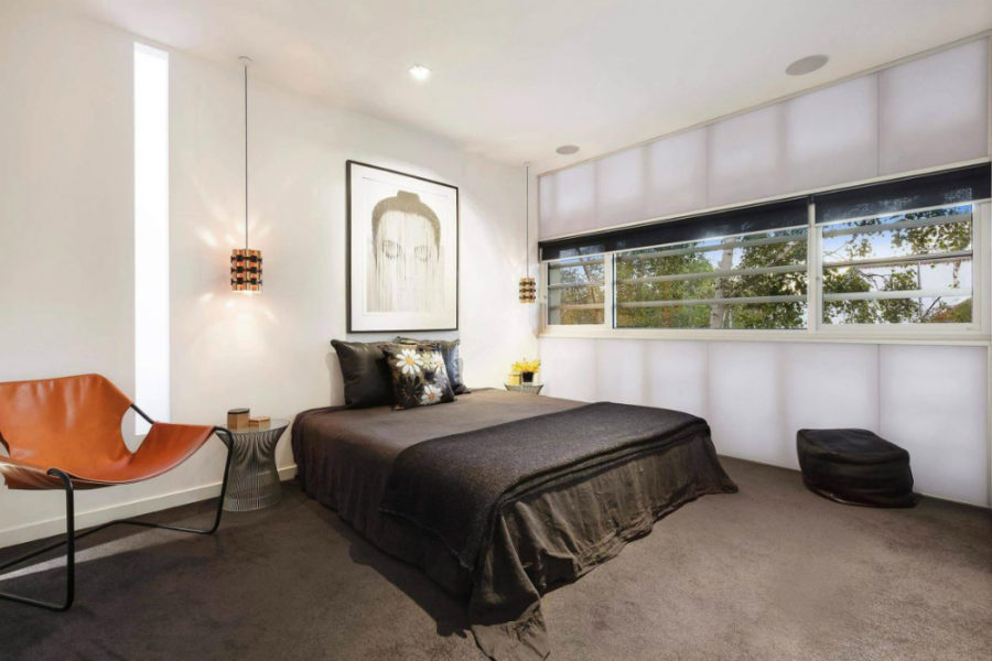 Minimalist bedroom uses artwork in place of a headboard