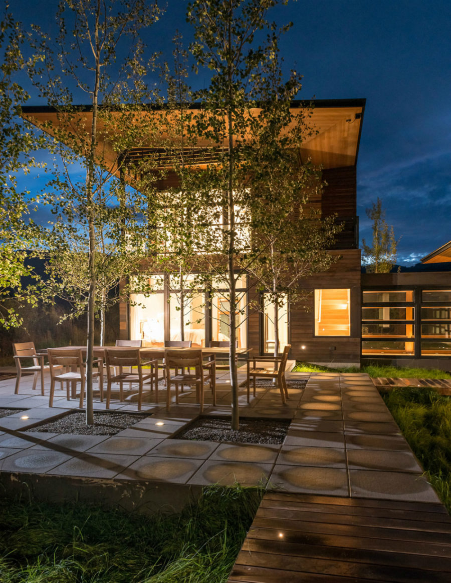 Outdoor dining room gets illlumination from numerous windows in the evening