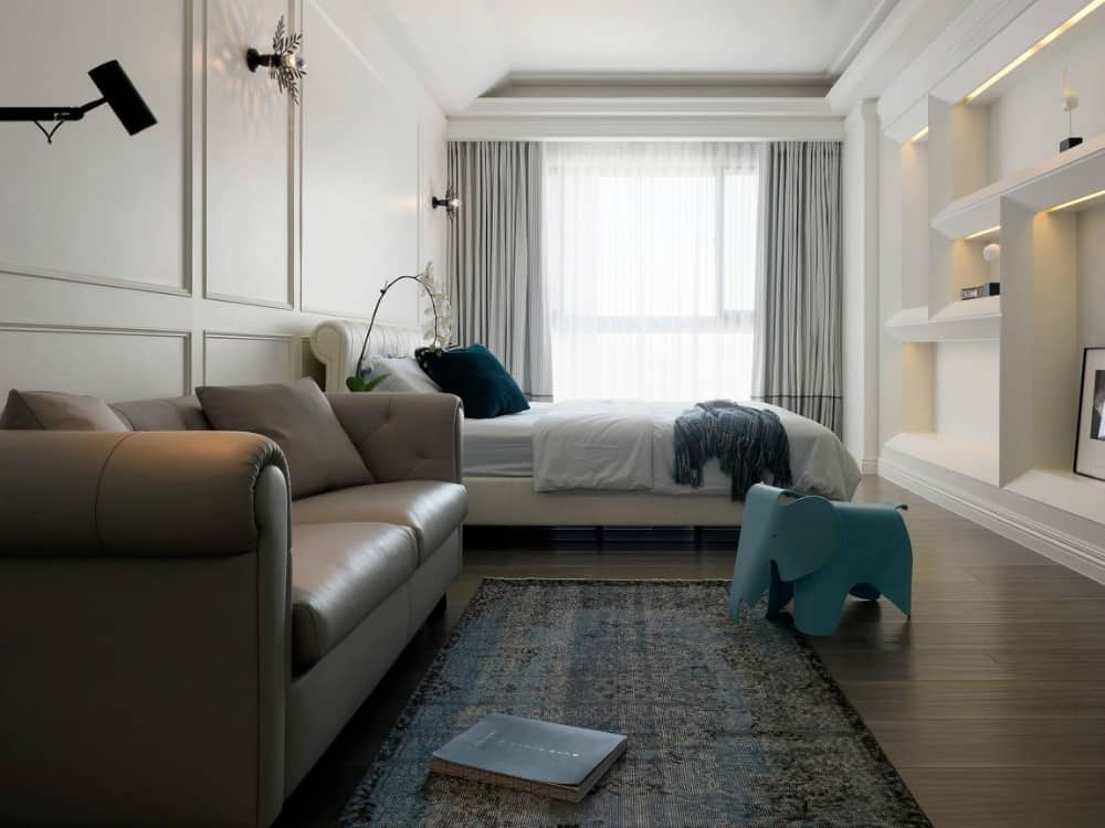 Palatial bedroom includes leather sofa and built-in assymetric wall shelving