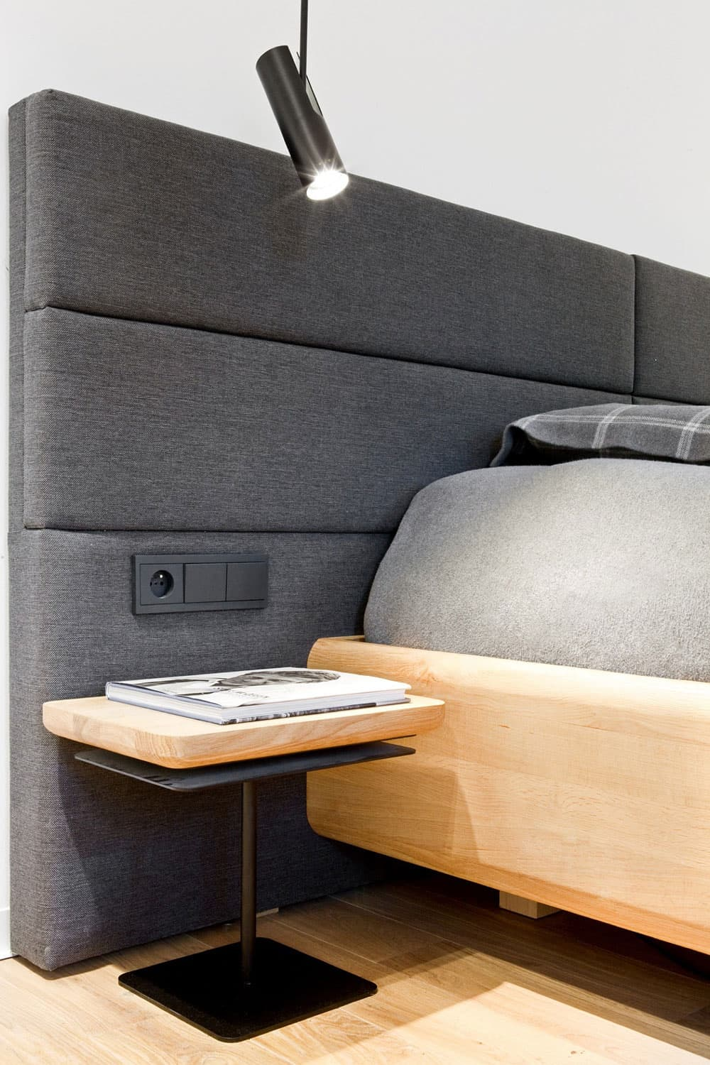Soft upholstered headboard includes an electric outlet and light switches