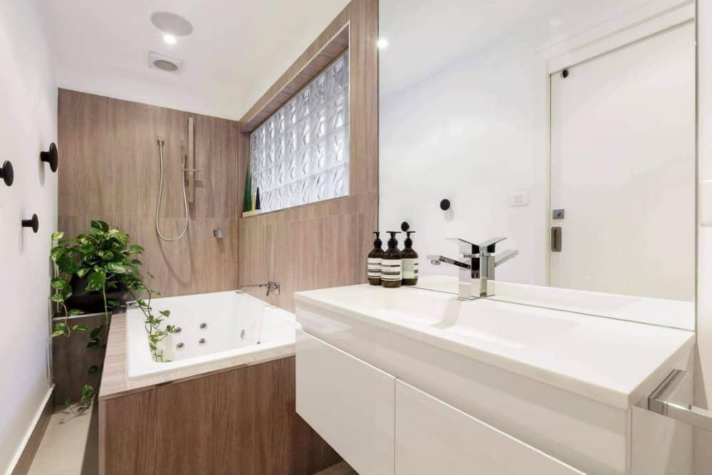 Spacious bathroom is half clad in wood