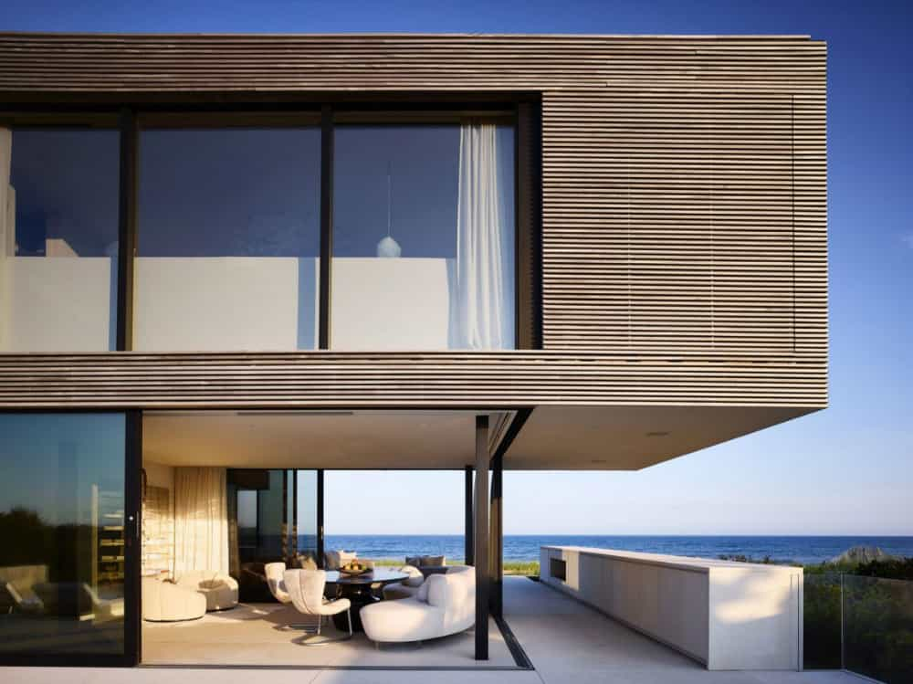 The glass-encased living area has views of the ocean