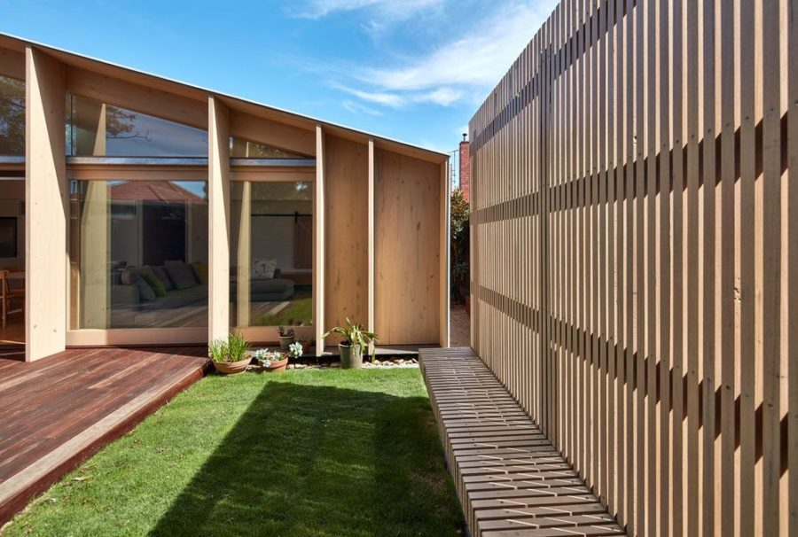 The wooden slat fence features a built-in bench