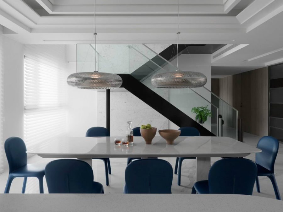 Two donut-shaped metallic pendants make a cool contrast with a marble table and leather chairs