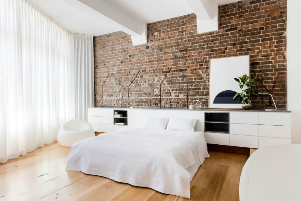 White apartment contrasts with old exposed brick