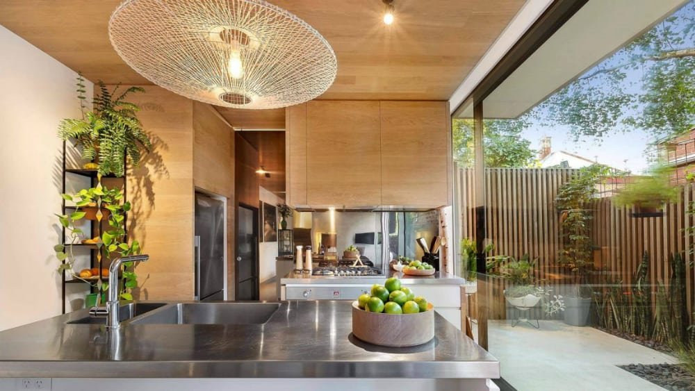 Wooden kitchen cabinets contrast with the stainless steel elements