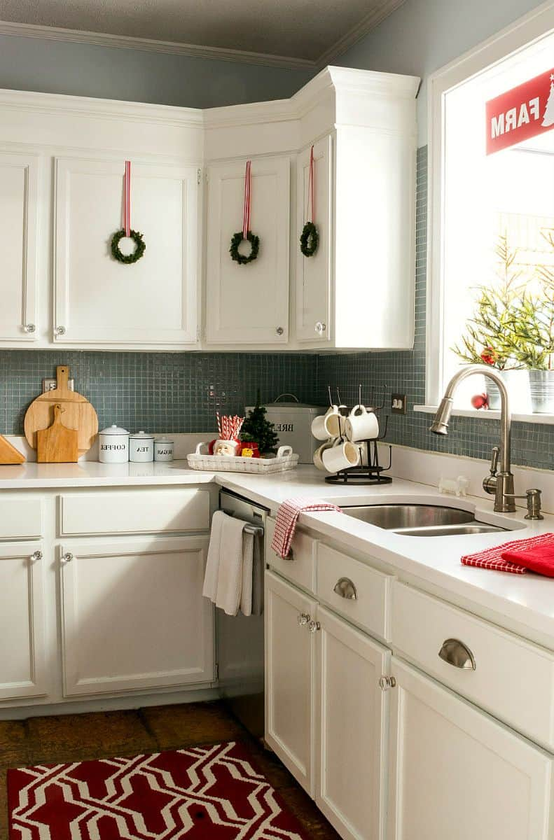 small wreaths on white cabinets in kitchen for christmas