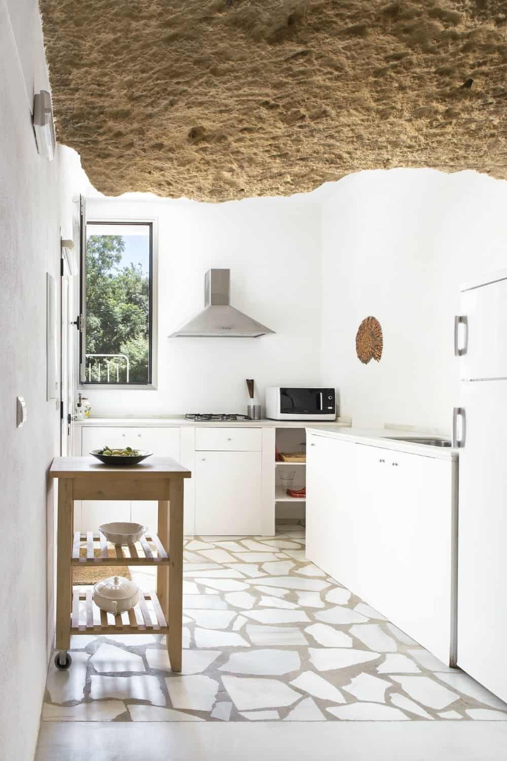 A window allows plenty of natural light in lighting up the white kitchen beautifully