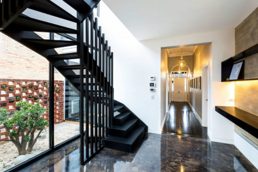 An architectural staircase makes a designing element in the hallway