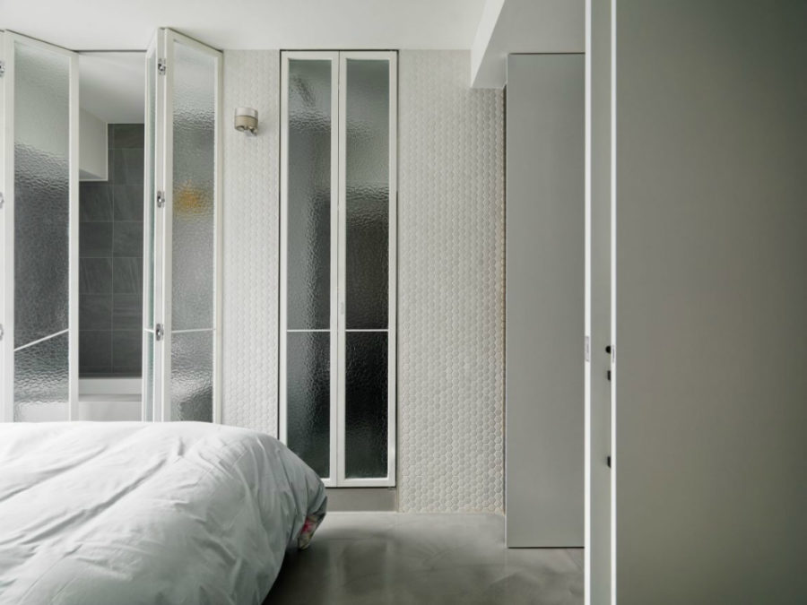 Beautifully light bedroom uses tiles and rippled glass to show off the bathroom