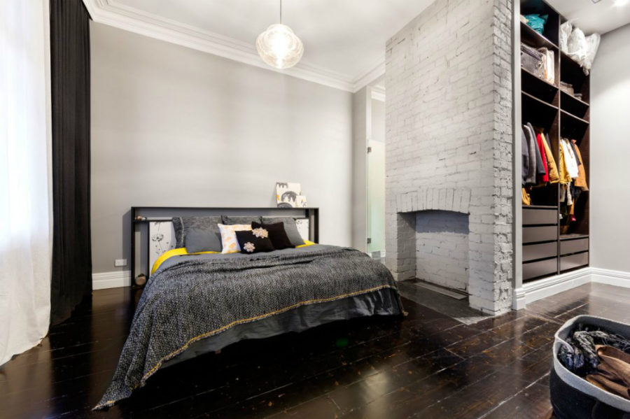 Bedroom features its own closet and a fireplace mantel