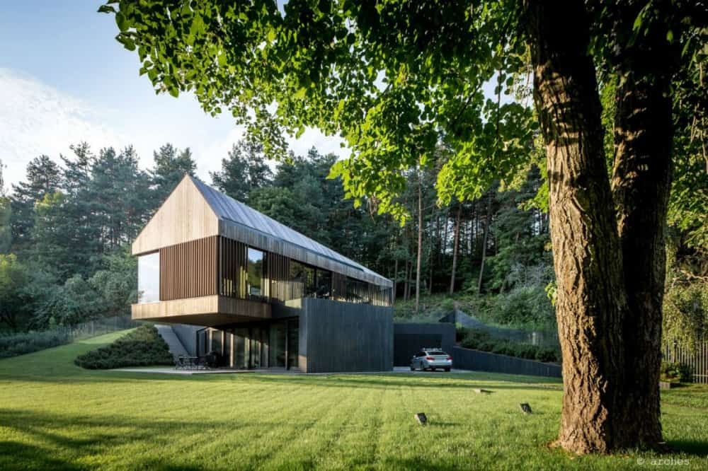 Cantilevering pitched roof house standsa support made of wood and glass