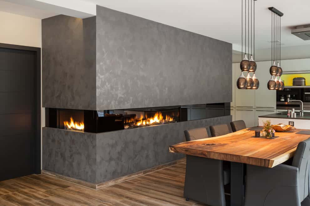 Dining room has not only got some fancy lights but also a wall-built glass fireplace