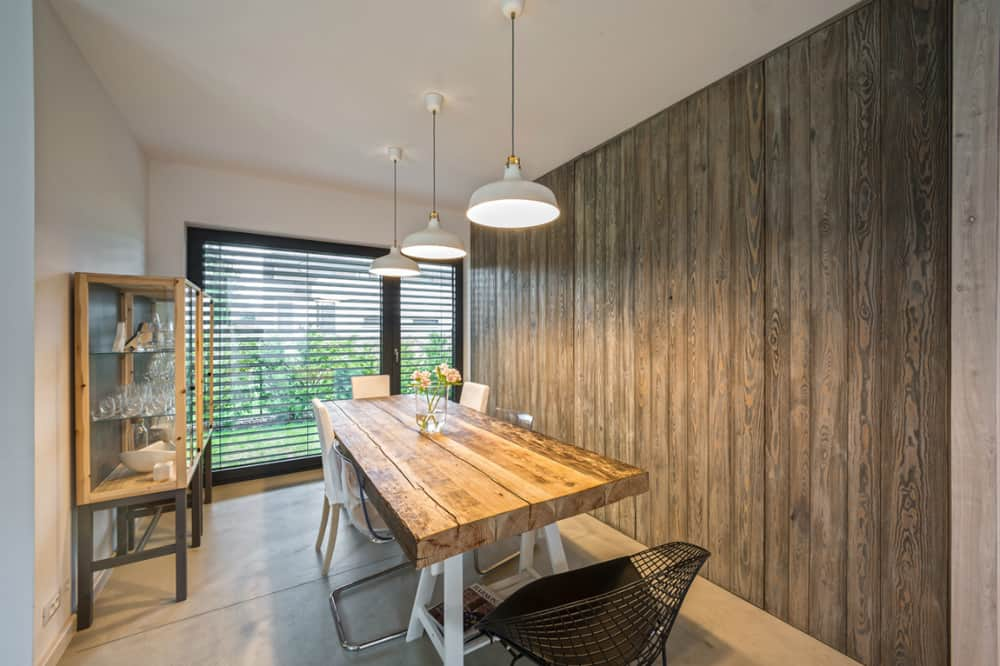 Dining room look cozy with a wooden feature wall