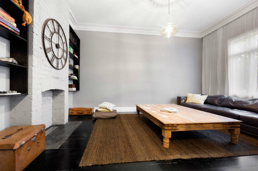 Elegant living room features exposed painted brick