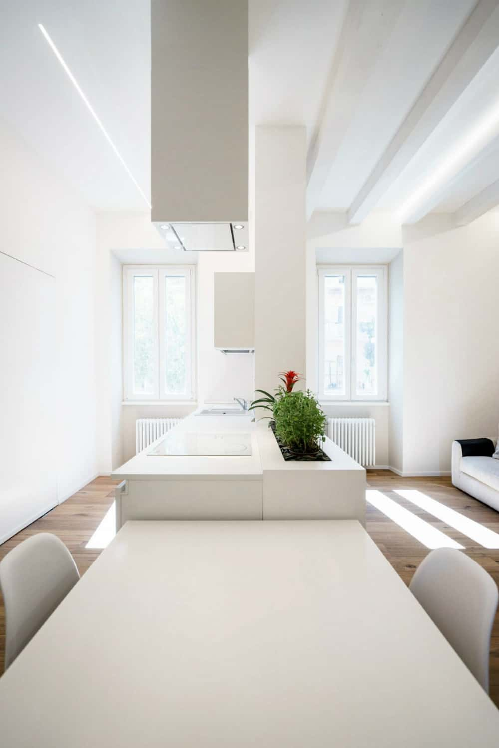 Kitchen worktops continue with a white dining table