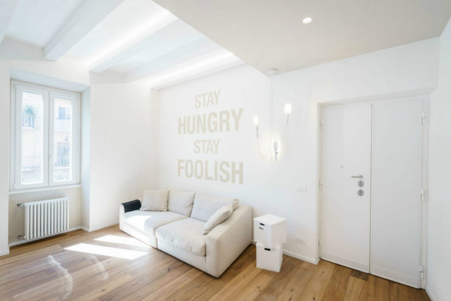 White living area has inspirational phrases on its feature wall 900x600 All White Ethereal House is a Space Efficient Apartment in Rome