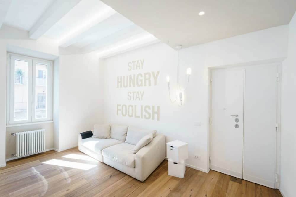White living area has inspirational phrases on its feature wall