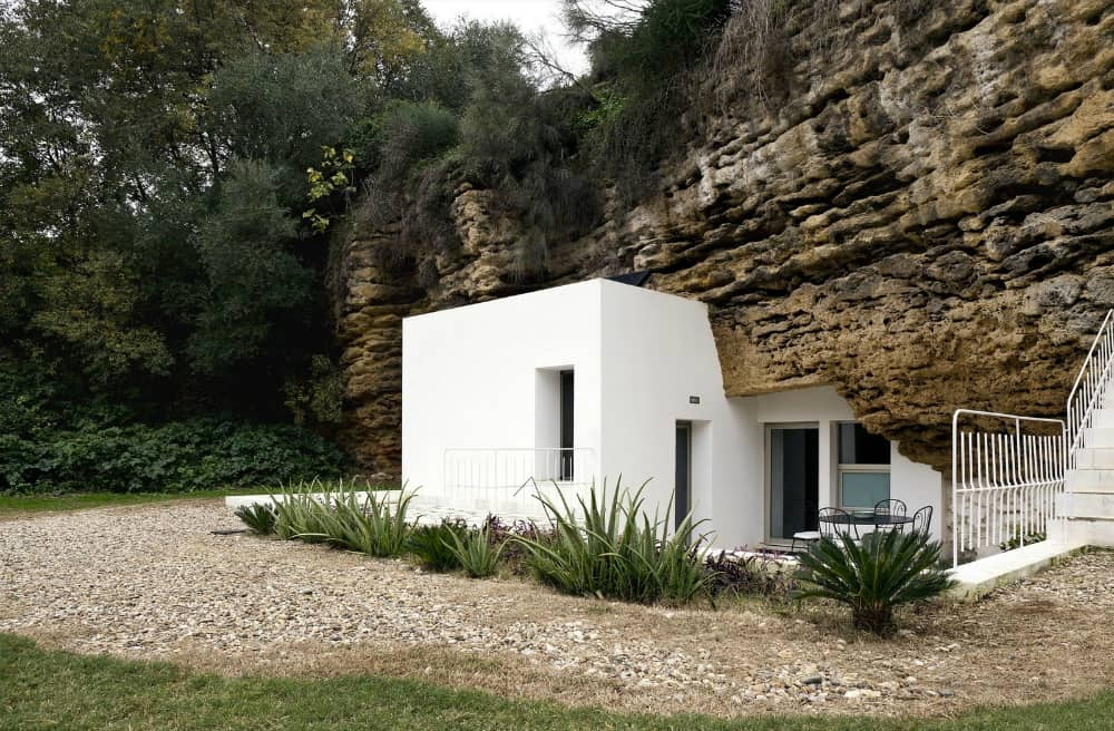 White plaster house architecture looks spotless next to discolored rock