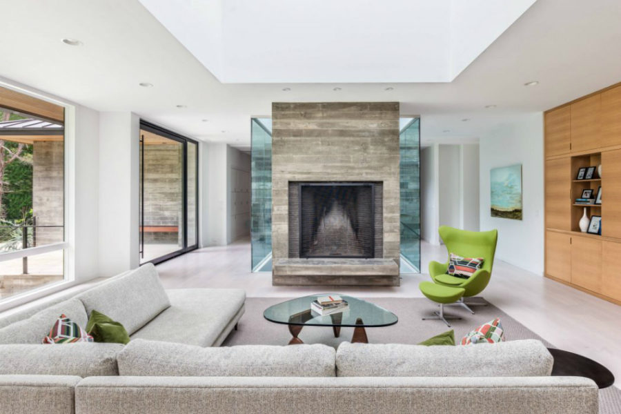A big fireplace is a stark contrast next to numerous glass inclusions 900x600 Modern Residence in South Carolina Filled with Light And Style
