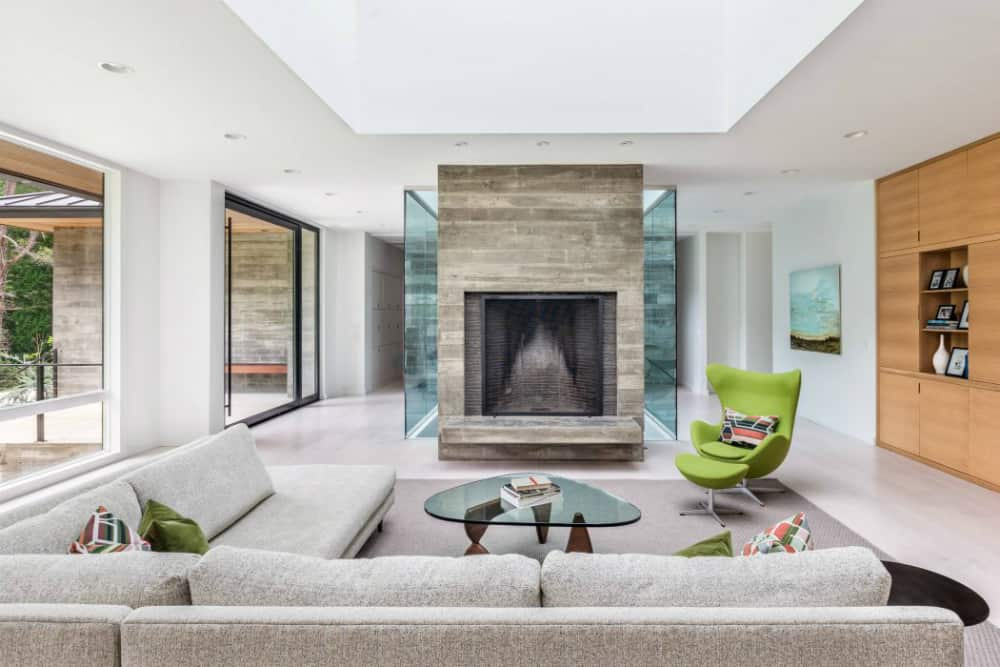 A big fireplace is a stark contrast next to numerous glass inclusions