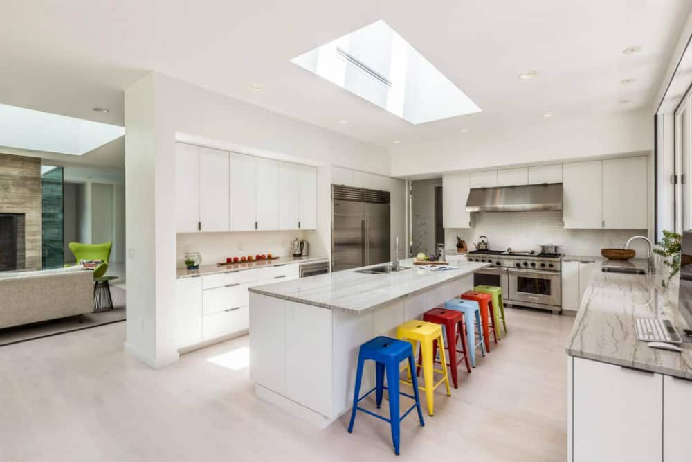 A white kitchen comes with colorful breakfast bar stools