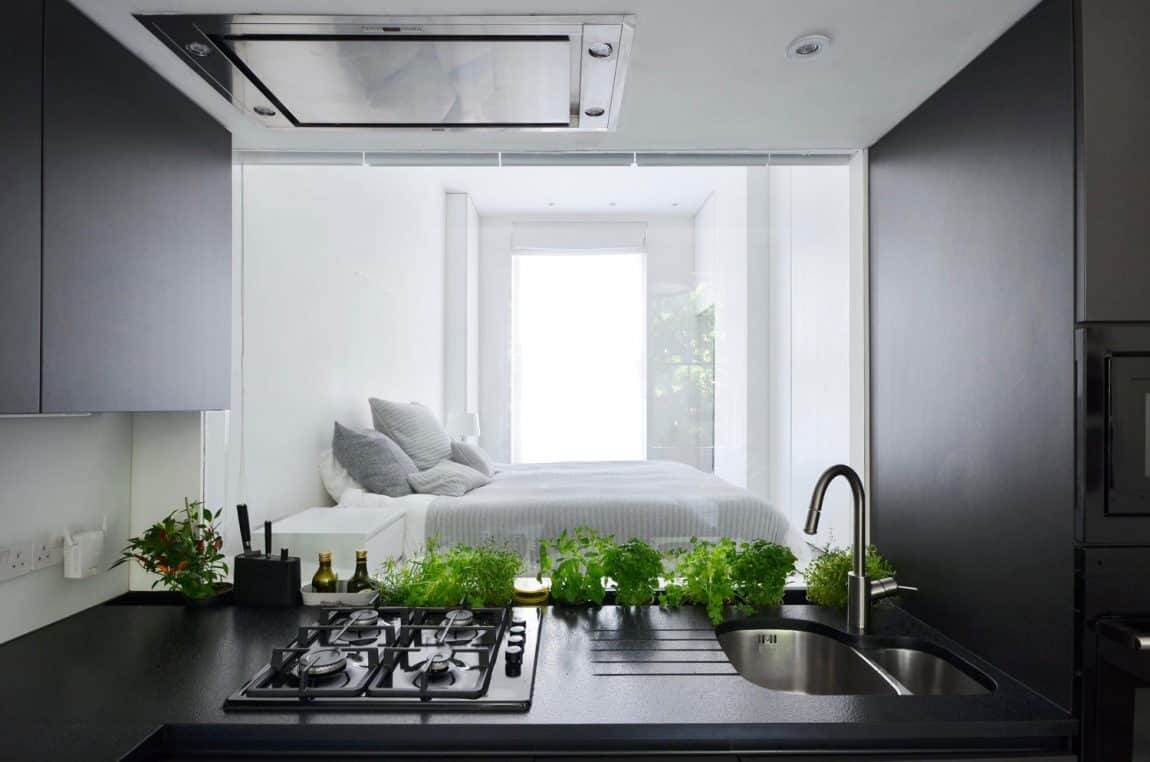 All-white bedroom especially stands out in the black kitchen frame
