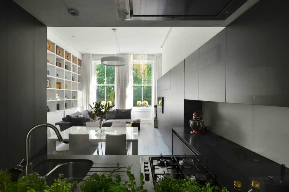 Black kitchen punctuates the modern white design