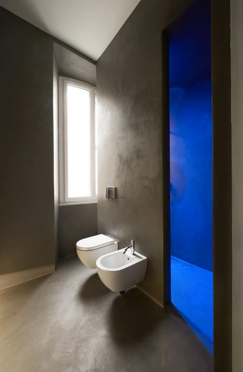 Blue lighting brightens up grey concrete in the bathroom