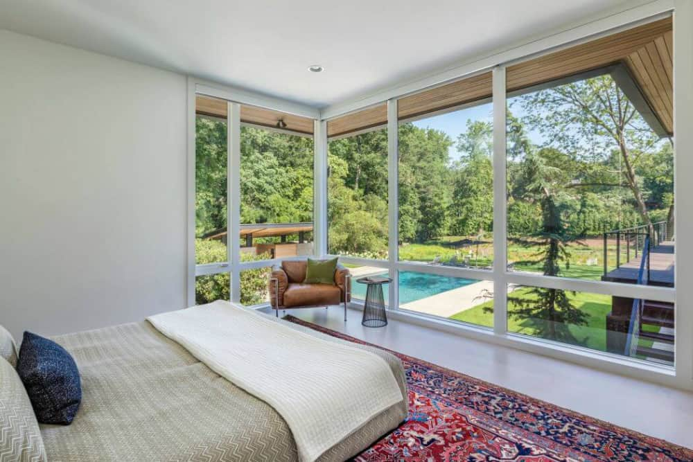 Corner window in the bedroom overlooks the shiny courtyard with a pool