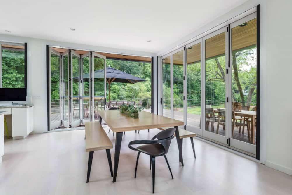 Dining room has an indoor-outdoor atmosphere thanks to glass walls