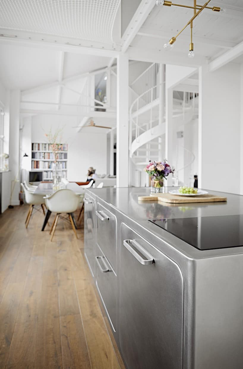Kitchen island with a cooking top has a visual connection to the stainless steel dining table French Loft With a Scandinavian Spirit