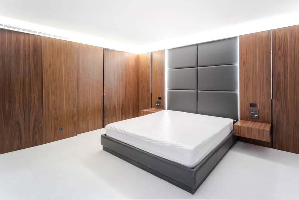 Leather bed frame and headboard is a focal point of a wood-clad bedroom
