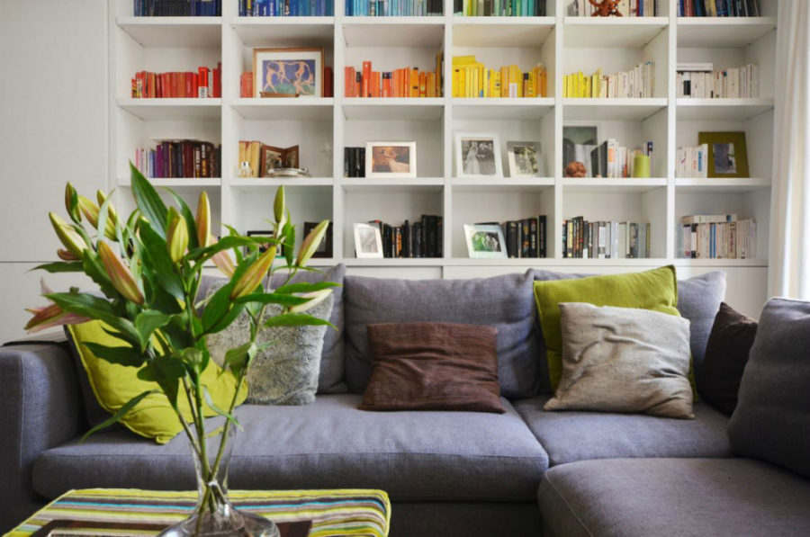 Living room storage wall makes for a colorful home library 900x597 Small London Apartment With an Interior Window That Makes a Huge Difference