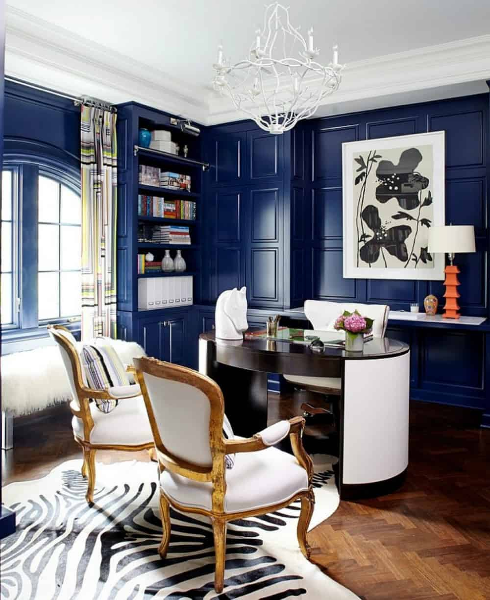 Modern home office with blue walls and wooden floors