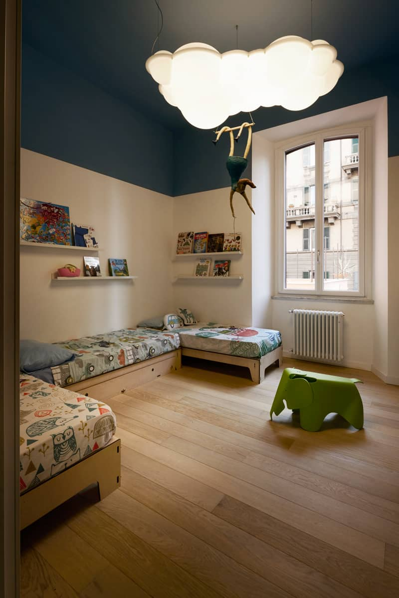 Shared kids room is a lot of fun thanks to creative chandelier and plenty of reading material