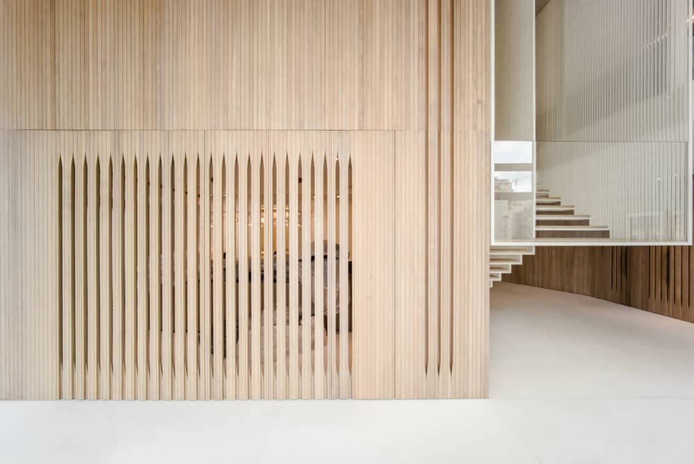 Slat double door separates different zones, creating the sense of rooms