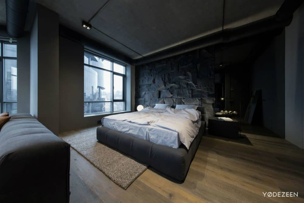 Trendy soft bed frame provides a contrast to the rough stone headboard wall