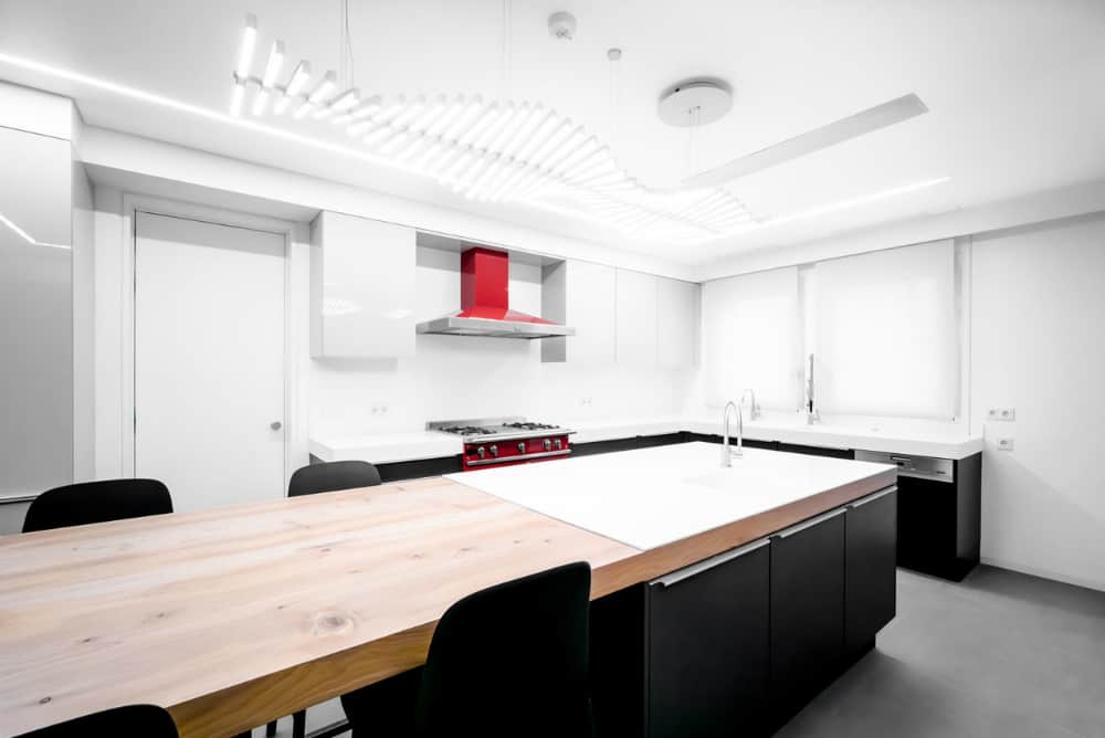 White kitchen benefits from a dark contrast of black cabinets and chairs and echoes the rest of the interior with a thick wooden countertop