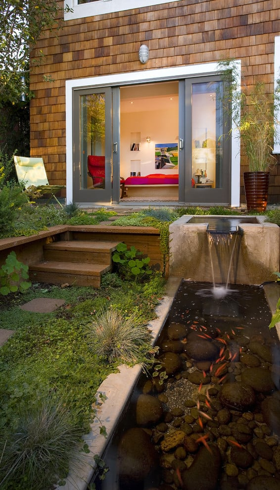 a-contemporary-patio-with-a-koi-pond-and-a-little-waterfall