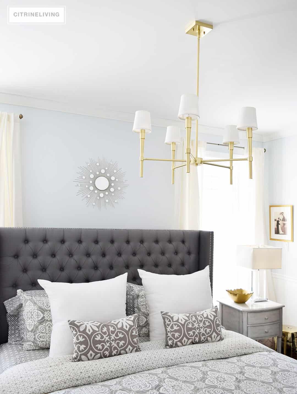 modern-brass-chandelier-bedroom-grey-bedding-pale-blue-walls