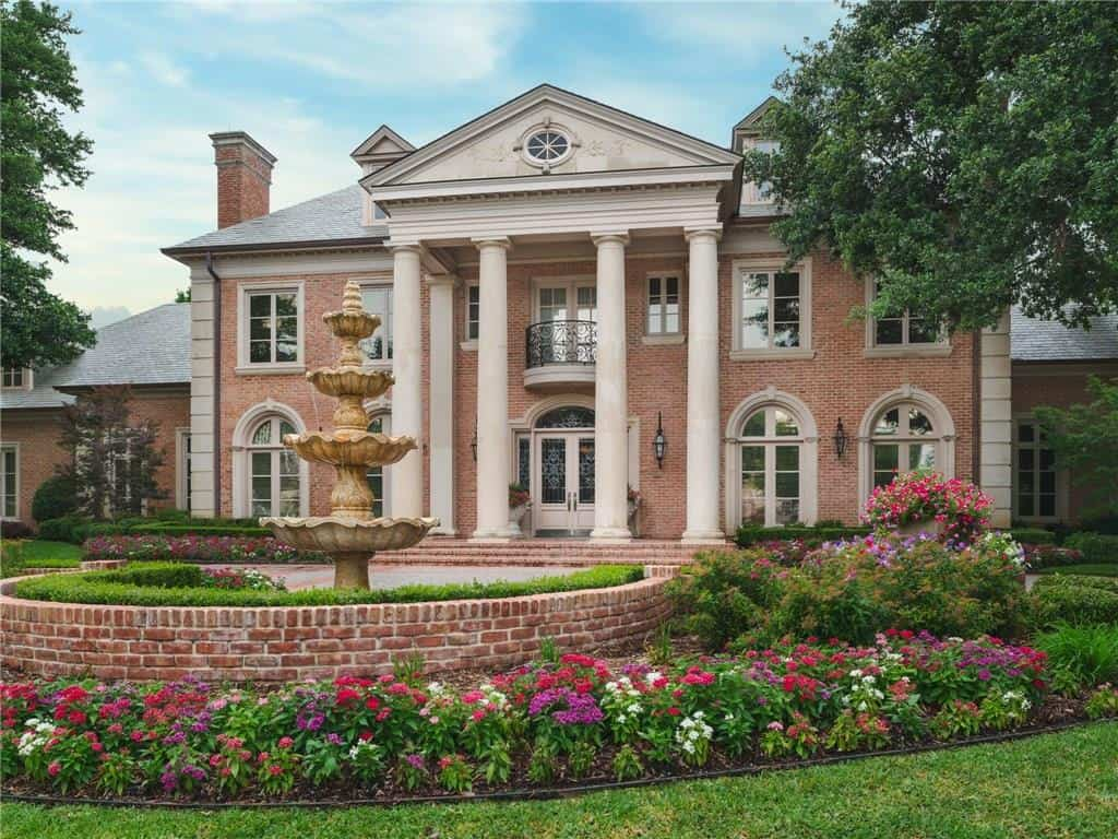 brick colonial style home with pillars