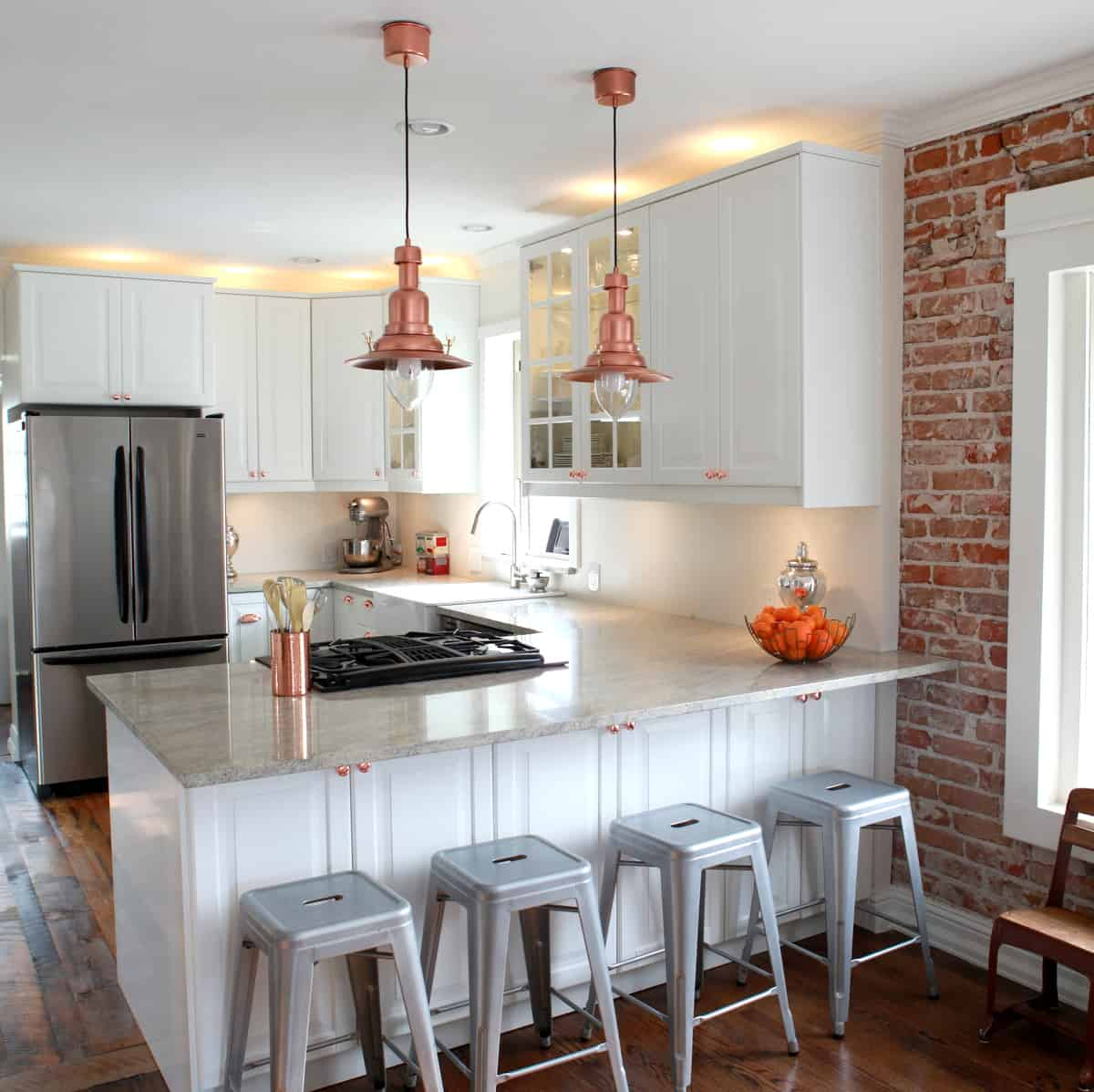 Although this kitchen is all white your focus goes directly towards the copper pendants.